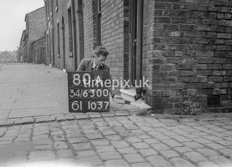 SD630080A, Man marking Ordnance Survey minor control revision point with an arrow in 1940s