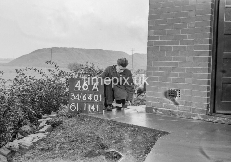 SD640146A, Man marking Ordnance Survey minor control revision point with an arrow in 1940s