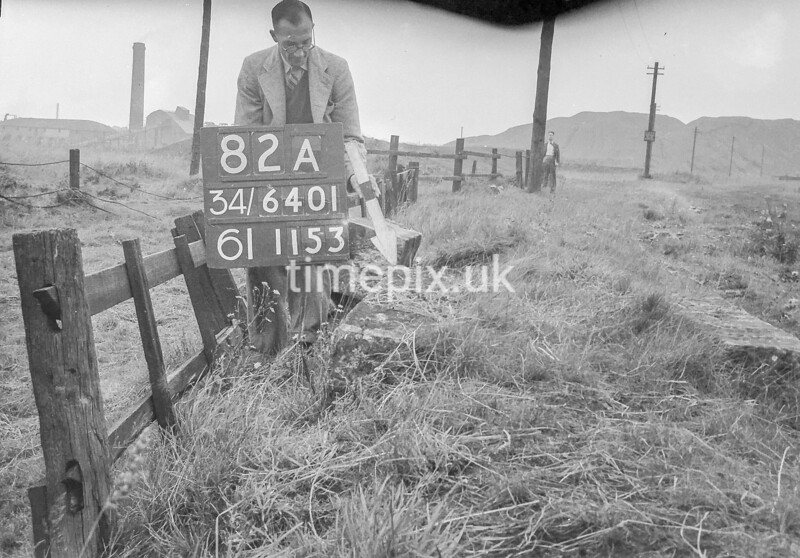 SD640182A, Man marking Ordnance Survey minor control revision point with an arrow in 1940s
