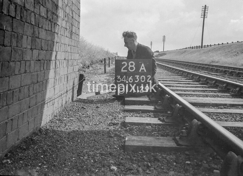 SD630228A, Man marking Ordnance Survey minor control revision point with an arrow in 1940s