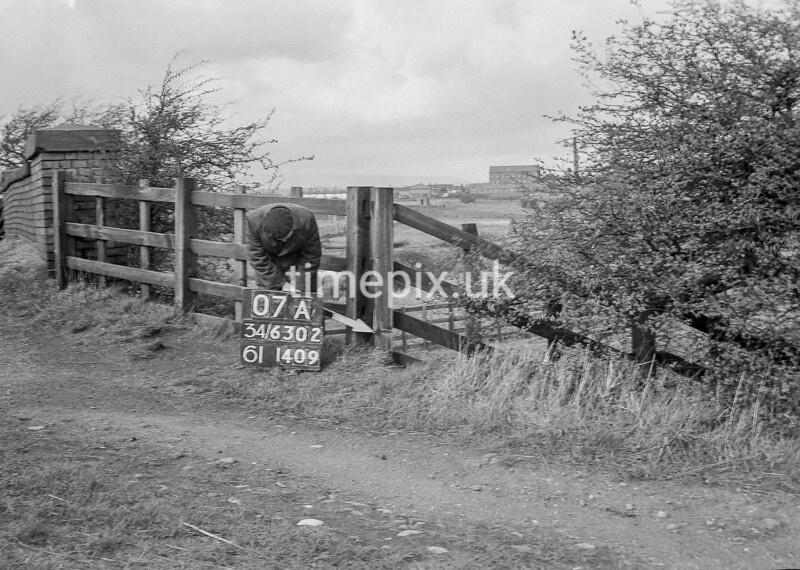 SD630207A, Man marking Ordnance Survey minor control revision point with an arrow in 1950s