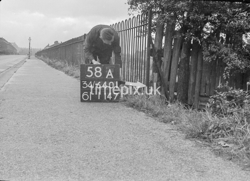 SD640158A, Man marking Ordnance Survey minor control revision point with an arrow in 1940s