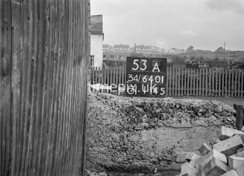 SD640153A, Man marking Ordnance Survey minor control revision point with an arrow in 1940s