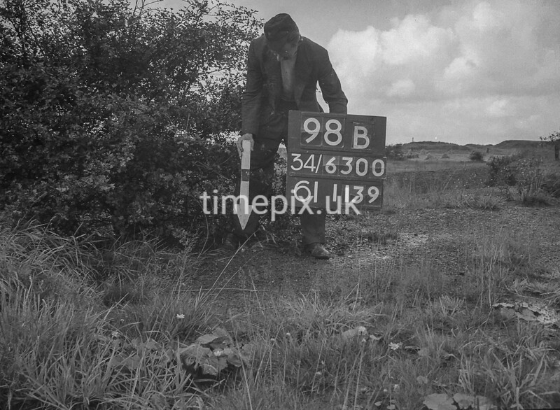 SD630098B, Man marking Ordnance Survey minor control revision point with an arrow in 1940s