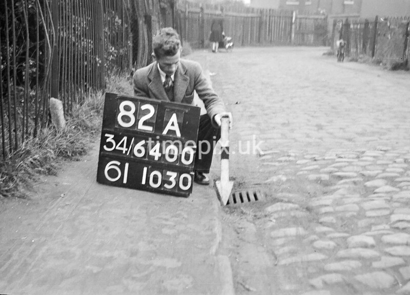 SD640082A, Man marking Ordnance Survey minor control revision point with an arrow in 1940s