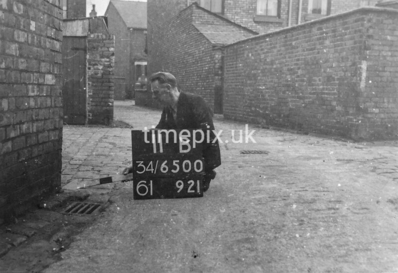 SD650011B, Man marking Ordnance Survey minor control revision point with an arrow in 1940s