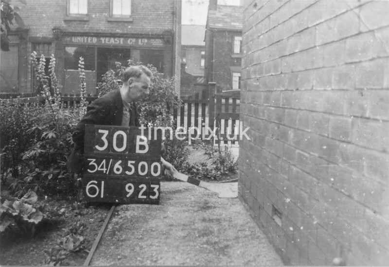SD650030B, Man marking Ordnance Survey minor control revision point with an arrow in 1940s