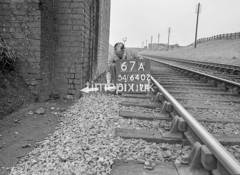 SD640267A, Man marking Ordnance Survey minor control revision point with an arrow in 1940s