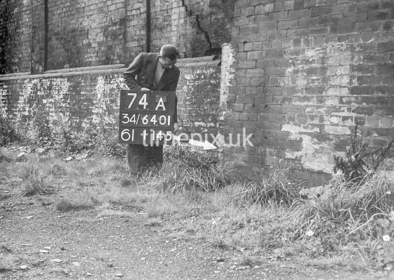 SD640174A, Man marking Ordnance Survey minor control revision point with an arrow in 1940s