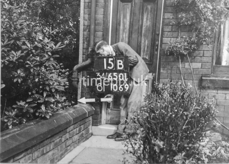 SD650115B, Man marking Ordnance Survey minor control revision point with an arrow in 1940s