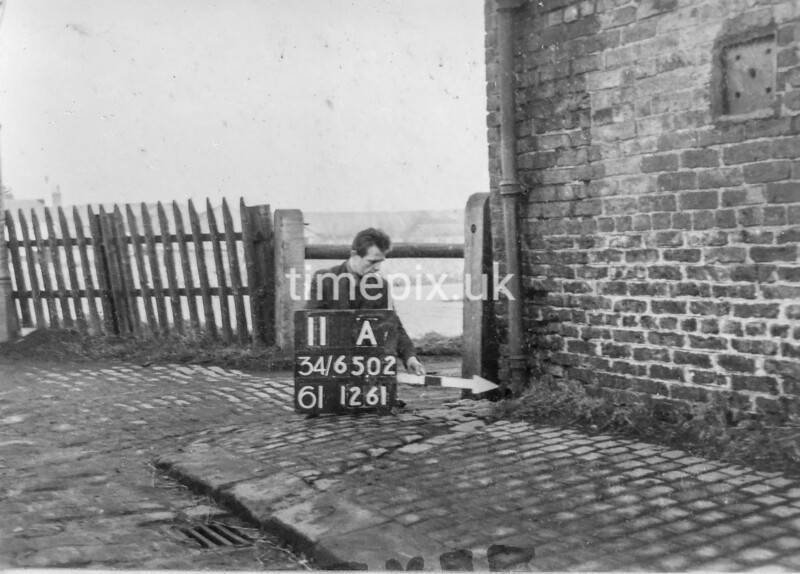 SD650211A, Man marking Ordnance Survey minor control revision point with an arrow in 1940s