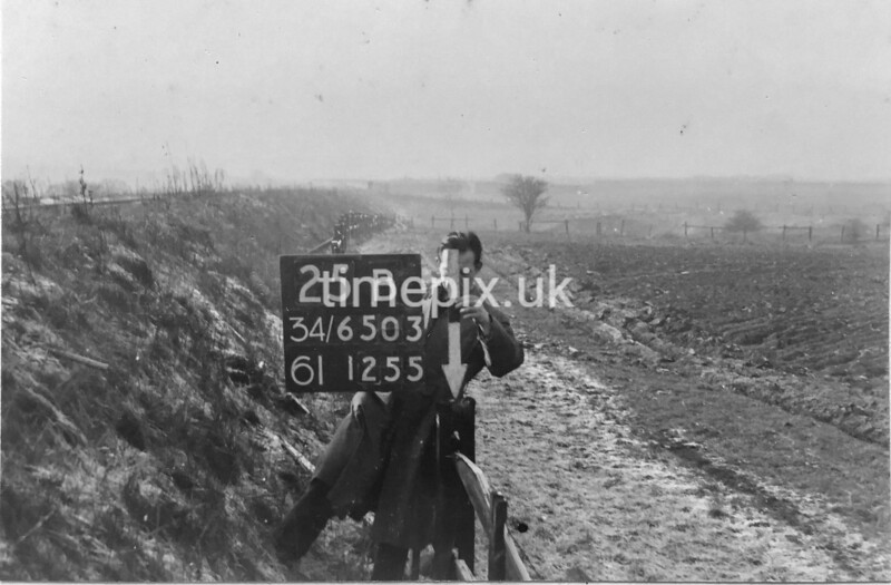 SD650325B, Man marking Ordnance Survey minor control revision point with an arrow in 1940s