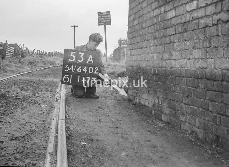 SD640253A, Man marking Ordnance Survey minor control revision point with an arrow in 1940s