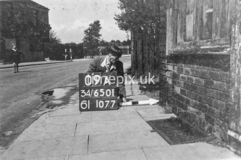 SD650109A, Man marking Ordnance Survey minor control revision point with an arrow in 1940s