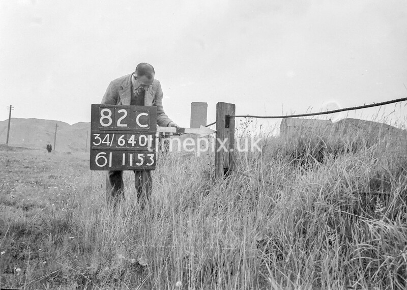 SD640182C, Man marking Ordnance Survey minor control revision point with an arrow in 1940s