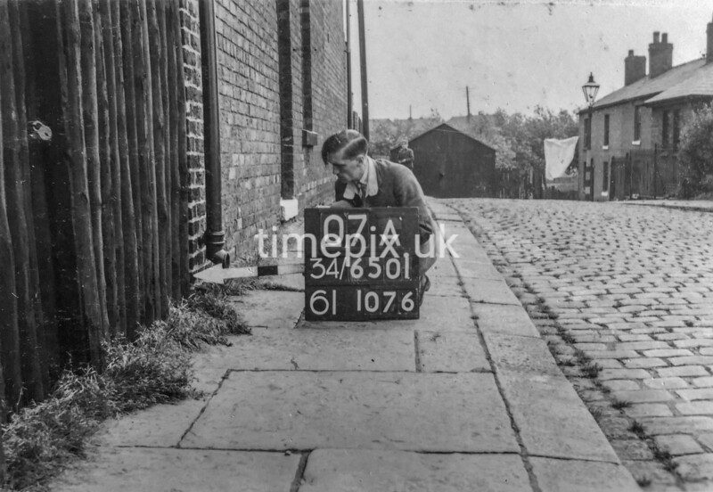 SD650107A, Man marking Ordnance Survey minor control revision point with an arrow in 1940s