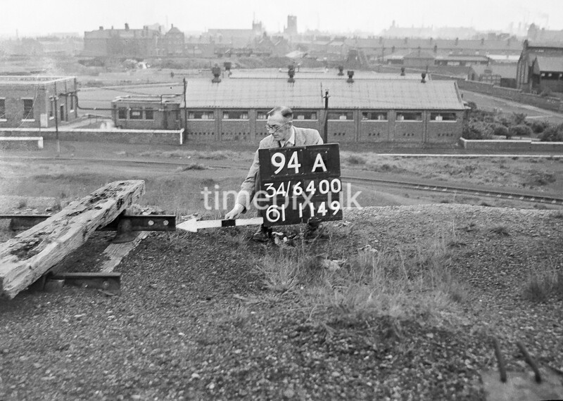 SD640094A, Man marking Ordnance Survey minor control revision point with an arrow in 1940s