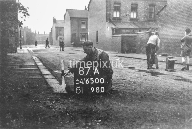 SD650087A, Man marking Ordnance Survey minor control revision point with an arrow in 1940s