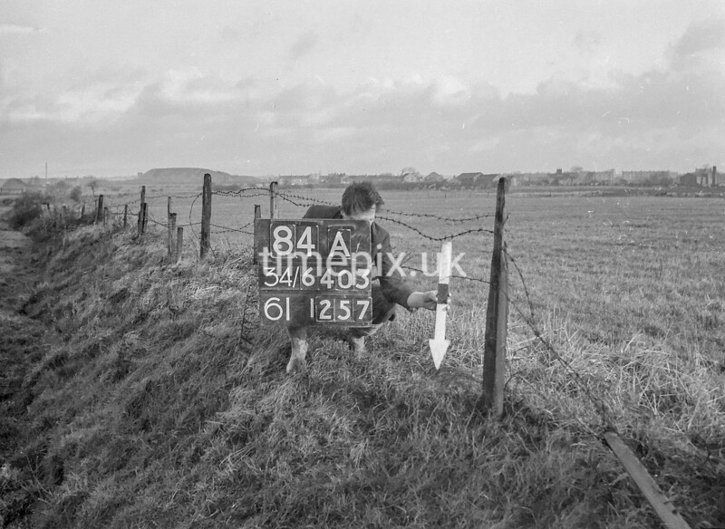 SD640384A, Man marking Ordnance Survey minor control revision point with an arrow in 1940s