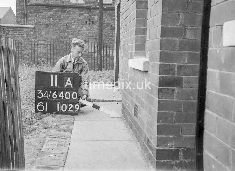 SD640011A, Man marking Ordnance Survey minor control revision point with an arrow in 1940s