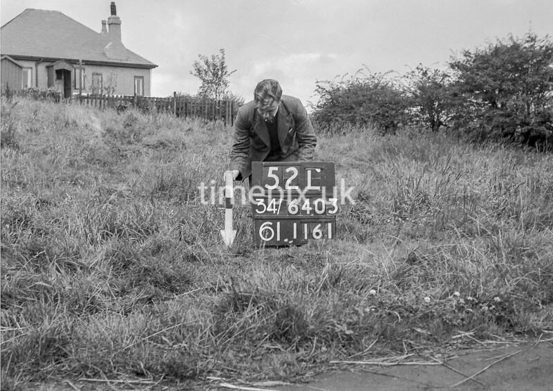 SD640352L, Man marking Ordnance Survey minor control revision point with an arrow in 1940s