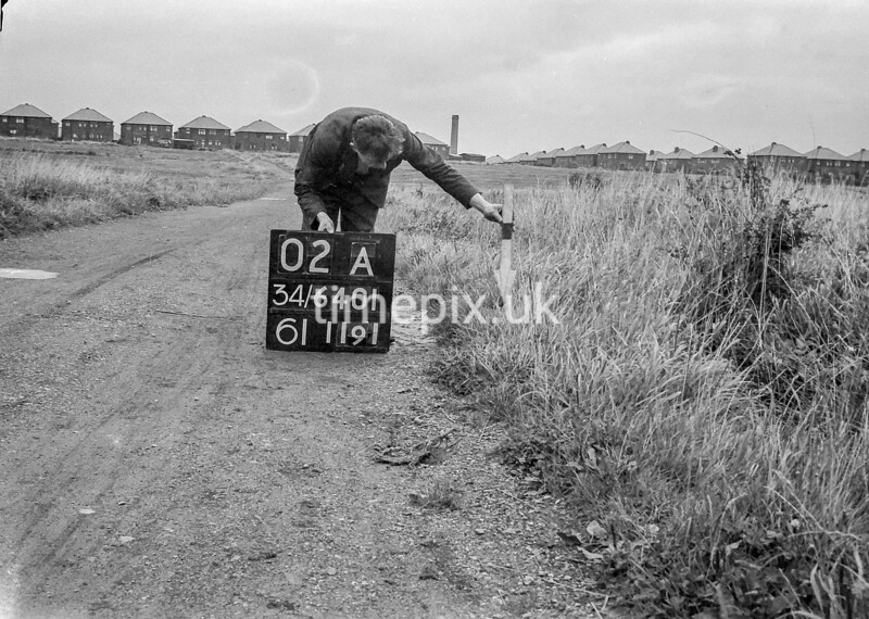 SD640102A, Man marking Ordnance Survey minor control revision point with an arrow in 1940s