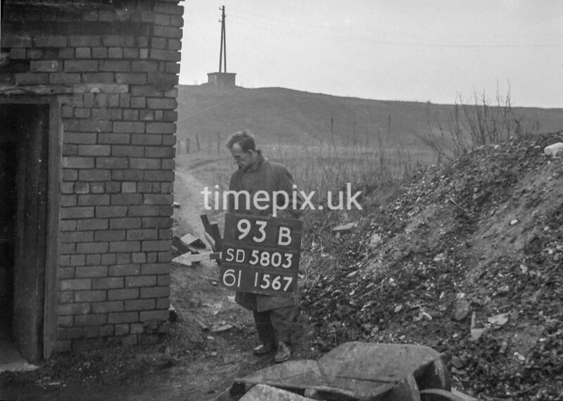 SD580393B, Man marking Ordnance Survey minor control revision point with an arrow in 1950s