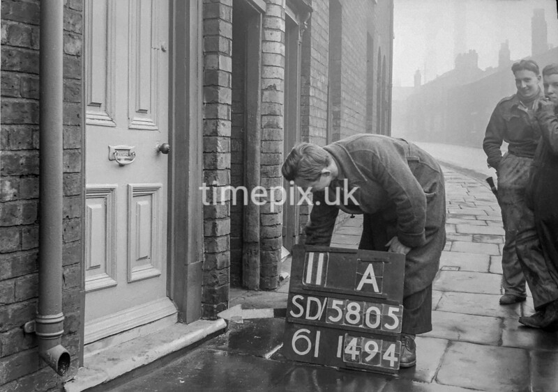 SD580511A, Man marking Ordnance Survey minor control revision point with an arrow in 1950s
