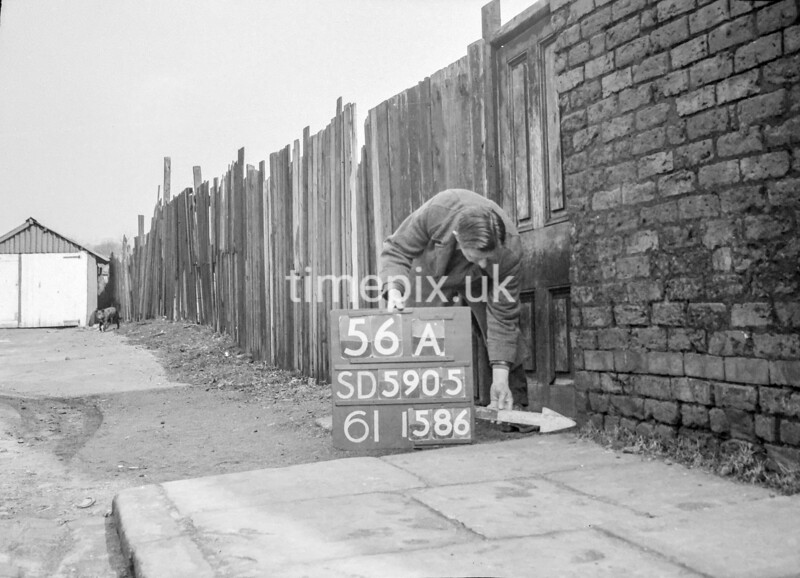 SD590556A, Man marking Ordnance Survey minor control revision point with an arrow in 1950s