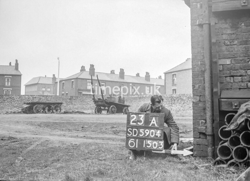 SD590423A, Man marking Ordnance Survey minor control revision point with an arrow in 1950s