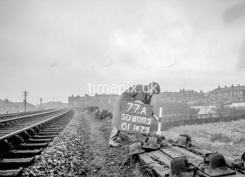 SD600577A, Man marking Ordnance Survey minor control revision point with an arrow in 1950s