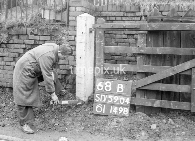 SD590468B, Man marking Ordnance Survey minor control revision point with an arrow in 1950s