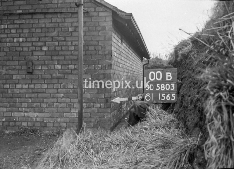 SD580300B, Man marking Ordnance Survey minor control revision point with an arrow in 1950s