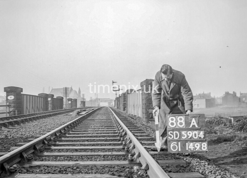 SD590488A, Man marking Ordnance Survey minor control revision point with an arrow in 1950s