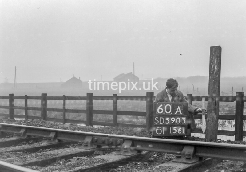 SD590360A, Man marking Ordnance Survey minor control revision point with an arrow in 1950s