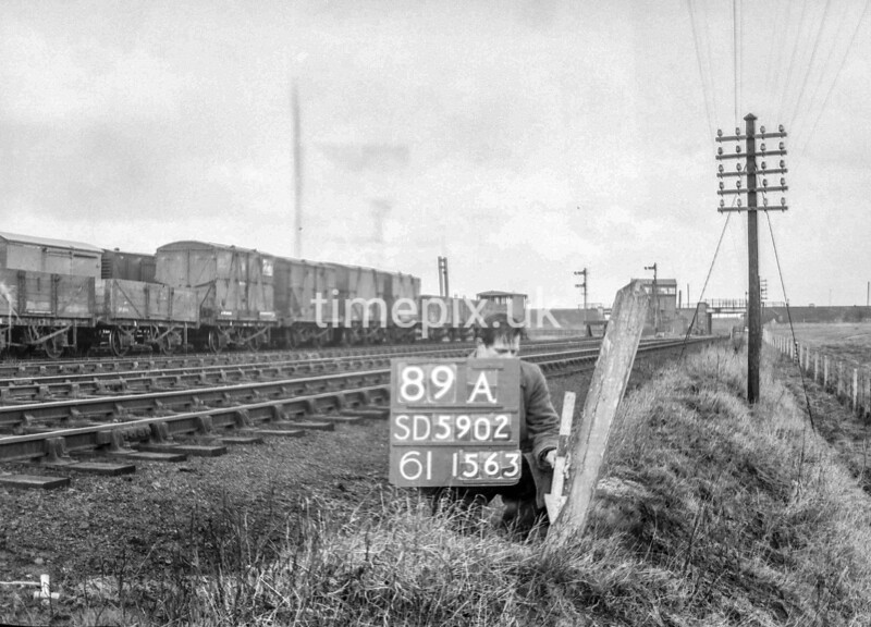 SD590289A, Man marking Ordnance Survey minor control revision point with an arrow in 1950s