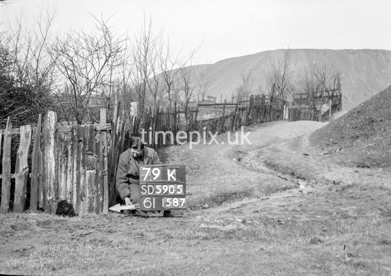 SD590579K, Man marking Ordnance Survey minor control revision point with an arrow in 1950s