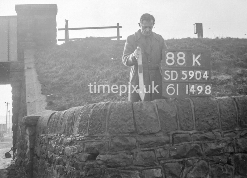 SD590488K, Man marking Ordnance Survey minor control revision point with an arrow in 1950s