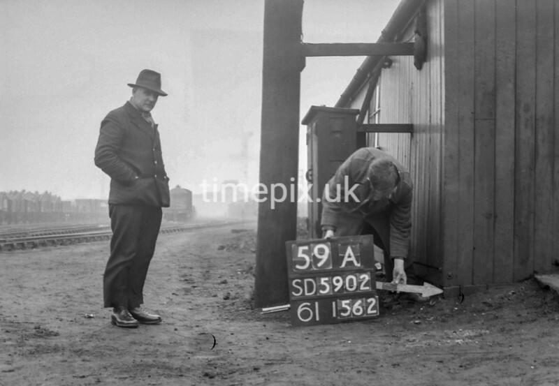 SD590259A, Man marking Ordnance Survey minor control revision point with an arrow in 1950s