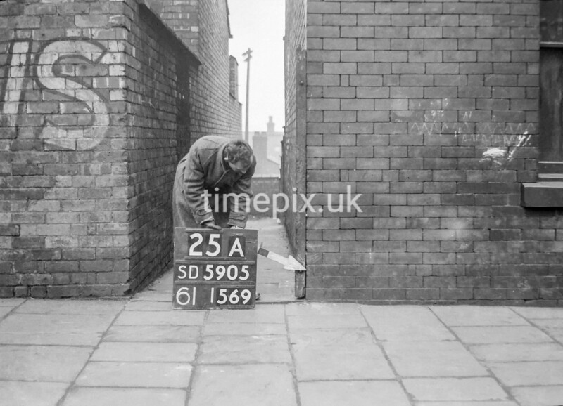 SD590525A, Man marking Ordnance Survey minor control revision point with an arrow in 1950s