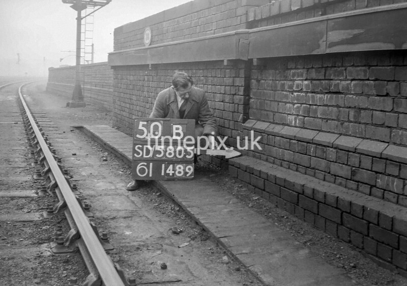 SD580550B, Man marking Ordnance Survey minor control revision point with an arrow in 1950s