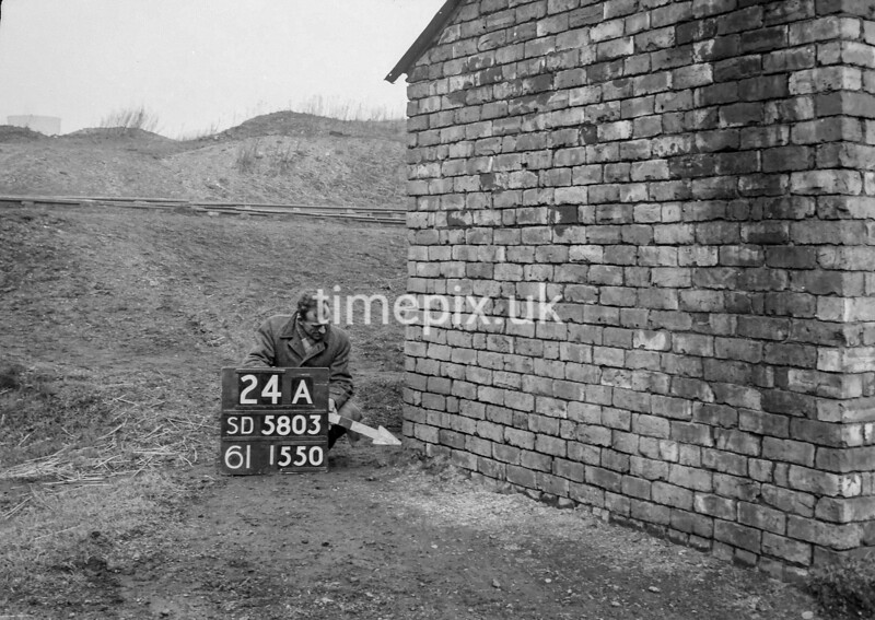 SD580324A, Man marking Ordnance Survey minor control revision point with an arrow in 1950s