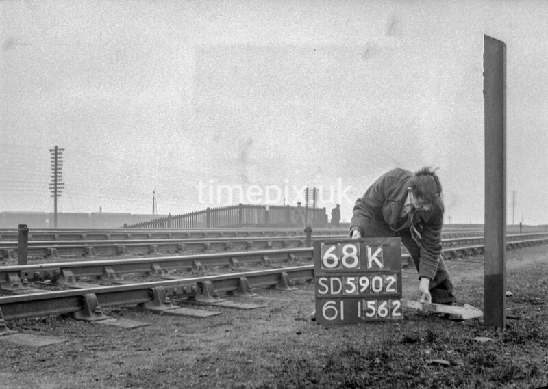 SD590268K, Man marking Ordnance Survey minor control revision point with an arrow in 1950s