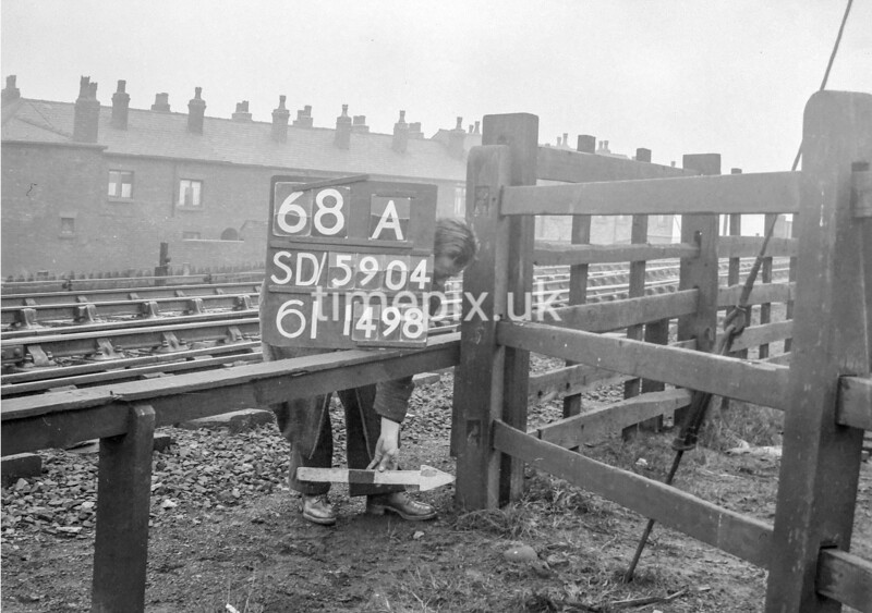 SD590468A, Man marking Ordnance Survey minor control revision point with an arrow in 1950s