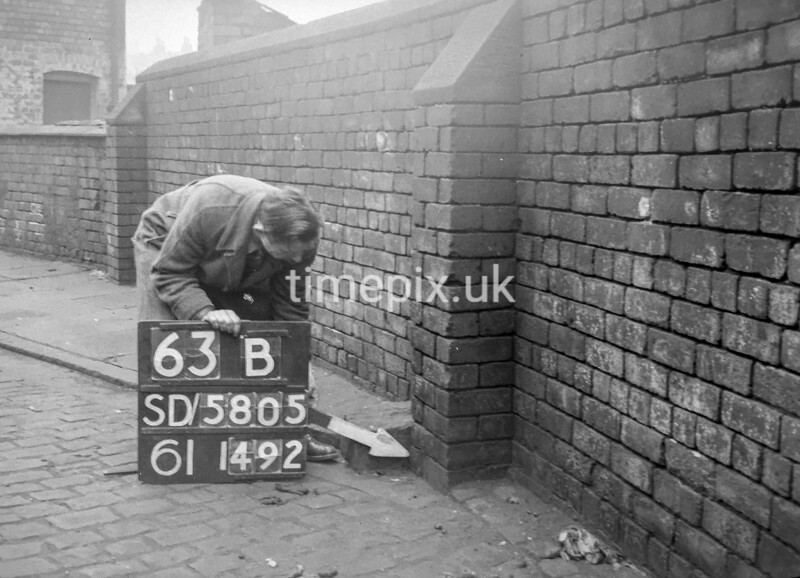 SD580563B, Man marking Ordnance Survey minor control revision point with an arrow in 1950s