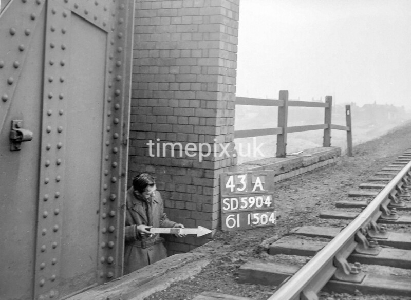 SD590443A, Man marking Ordnance Survey minor control revision point with an arrow in 1950s