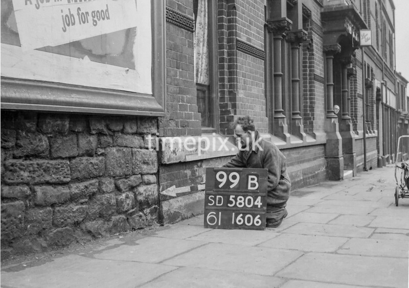 SD580499B, Man marking Ordnance Survey minor control revision point with an arrow in 1950s