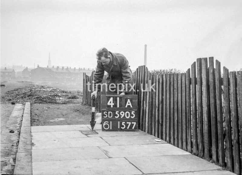 SD590541A, Man marking Ordnance Survey minor control revision point with an arrow in 1950s