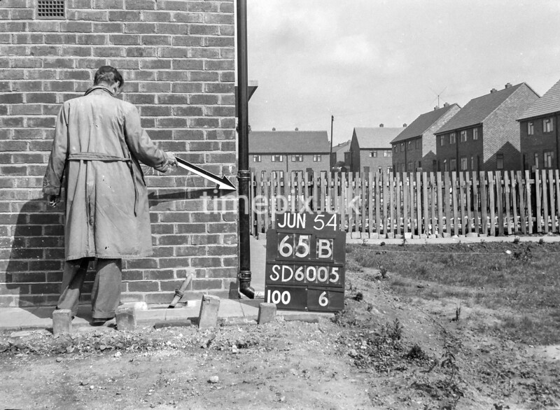 SD600565B, Man marking Ordnance Survey minor control revision point with an arrow in 1950s