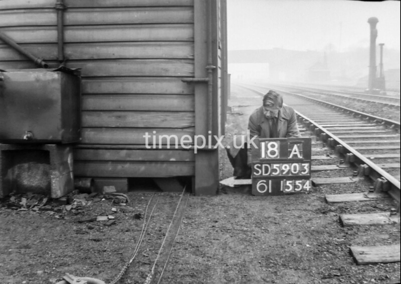 SD590318A, Man marking Ordnance Survey minor control revision point with an arrow in 1950s